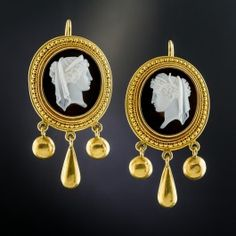 A noble pair of translucent white skin classical beauties are masterfully hand carved in opposing profiles against a glossy black onyx backdrop in these consummate Victorian hardstone cameo ear drops framed in classic Etruscan Revival style, each supporting a trio of golden dangles. Elegantly hand fabricated in rich 18K yellow gold, they drop 1 and 11/16 inches from the ear wires.