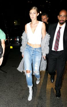 Gigi Hadid wears a grey jacket, white T-shirt, blue jeans, and