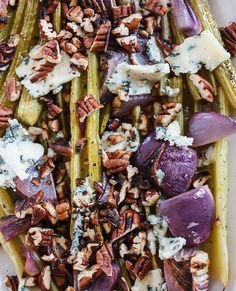 Celery stalks are braised in garlic flavored broth and topped with blue cheese and toasted pecan for texture.