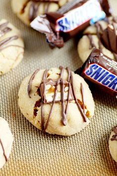Puffy clouds of soft and chewy peanut butter cookies topped with a snickers and a semisweet chocolate drizzle.