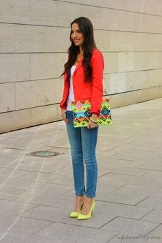 Orange-red blazer, white shirt, light jeans, neon pumps, neon colored purse