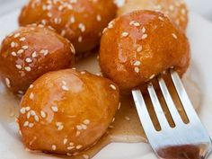 Greek Loukoumades are traditionally served at festivals and carnivals. Eaten while still warm, they are made by deep-frying sweet dough balls and then drizzling with honey syrup. The loukoumades are then sprinkled with sugar, cinnamon, walnuts or sesame seeds.
