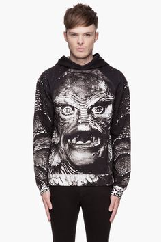 Long sleeve hooded sweatshirt in tones of grey and black. Universal Studios Creature From The Black Lagoon_themed print throughout. Raglan s...