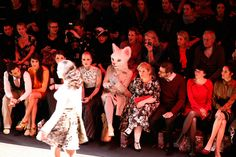 Getty Images for IMG AVANT-GARDE: Fashion fans, including one wearing a cat headpiece, sat in the front row of Rebekka Ruetz's show at Mercedes-Benz Fashion Week in Berlin Tuesday.