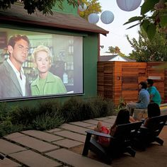 a white canvas tarp for movies was such a hit that they permanently linked their entertainment system to a projector via underground cables. Lounge area has seating for 12, a fire pit w/ room for plates & glasses. there is a big, living-room-style sofa that works outdoors. For extra guests, cushions are placed on the lid of their kids' old sandbox.