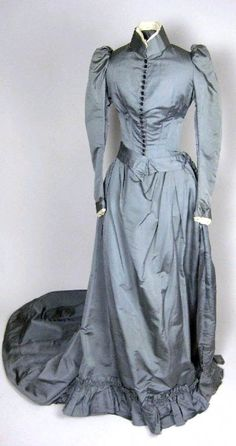 Day dress, ca. 1889-90. Blue-gray silk. Boned bodice has high neck and front button closure. Skirt slightly draped in front. Short train. Brightwells