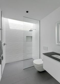 grey flooring Grey floor tiles have been paired with textured white tiles to create a contemporary bathroom, while a skylight located above the shower adds a touch of natural light to the space.