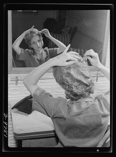 Safe clothes for women war workers. The importance of keeping hair short and neat for industrial war work cannot be over-emphasized. Here Eunice Kimball, Bendix employee, gives a final pat to her newly-dressed hair. Bendix Aviation Plant, Brooklyn, New York Photographer Ann Rosener Created March 1943