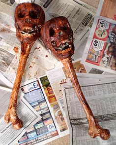 Maybe dollar store plastic bones and skulls glued together ( imagine one bone end would have to be cut off to fit into the bottom of the skull. ) then they are stained or painted with a brown / red wash.