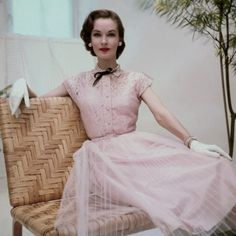 June 1952, Model is wearing a pink cotton lace dress and gloves.