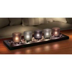 Bring soft illumination and classic style to any area of your home. This decorative set features 5 solid glass votive holders in beautifully muted hues. The candle holders rest decoratively amid an attractive espresso wood base.