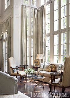 Pale gray walls and soaring windows set the tone for this lovely, neutral space. - Photo: Emily Jenkins Followill / Design: Patricia McLean
