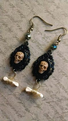 Made by yours truly ~ these lovely and dainty skull earrings feature a framed skull with a dangle bone. Lovely light weight and Perfect for