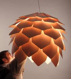 Check out this lamp by designer Pavel Eekra. There's no internal frame, just the 56 plates and screws configured in the pinecone form. Natural birch veneer is slightly transparent, which give…
