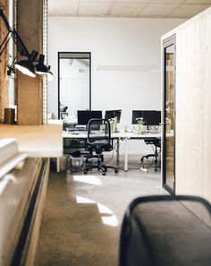 Project: Teamleader - Open work space. The open work spaces are seperated by wooden booths: Phone- and focusbooths. The combination of the concrete floor and ceiling with the wooden boxes make this place look industrial and warm at the same time.