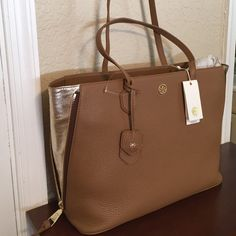 """Tory Burch Robinson """"Side-Zip"""" Tote. NWT HOST PICK 11/15  GORGEOUS Robinson leather side-zip tote bag color, Tigers Eye & Gold. Design with side zipper to expand to a larger size and expose the gold leather inserts. The leather is pebbled and exquisite. Interior has 1 large zip slip pocket, other side has 2 open slip pockets.  Top has magnetic closure with gold hardware. Also for sale in Black with luggage inserts. Measurements 9-1/2"""" Handle Drop.  18-1/2"""" expanded sides, 14-1/2"""" closed…"""