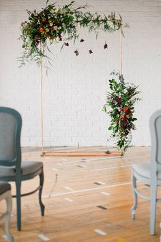 A simple and modern floral wedding arch with lush roses and greenery for an industrial themed wedding.