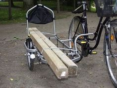 a bicycle side loaded with long pieces of wood