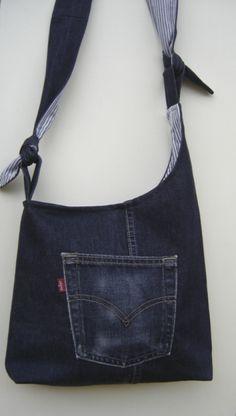 Újrahasznosított anyagból, (kinőtt farmernadrág) kék csíkos béléssel készült ez a jól kihasználható táska. Fiatalos, lendületes, kényelmes viselet. Elejére és a belsejébe a nadrág zsebeit használtam fel. Záródása mágneszár. Vállpántja megkötős megoldással készült, így tetszőleges hosszúságra állíthatod. Vállon és keresztbe átvetve is hordható. Mérete: szélessége 34/31 cm magassága az ív alsó részéig 31 cm talprésze 8 cm. Fül hossza a fényképen megkötve 92 cm. Bátran mosható...
