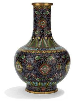 CHINE - XXe siècle. Vase de forme bouteille en bronze doré et émaux cloisonnés à décor de fleurs de lotus dans leurs rinceaux sur fond noir, l'épaulement orné de feuilles de bananiers. (Cabossé). H. : 26 cm.