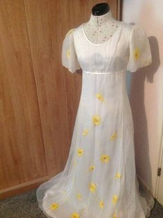 A beautiful, floaty summer wedding dress-perfect for spring and summer weddings!  This vintage wedding dress is from the 1970s but is in the regency period style so would look perfect at both modern and vintage style weddings. The dress is a UK size 10 (European size 38). The dress is floor length with no train. There are yellow flowers adorning the dress along the front and the sleeves. The back of the dress is plain. The sleeves are cap style sleeves made from a sheer, chiffon fabric. The…