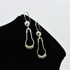 Keep it clean with a pair of silver shower curtain ring-inspired dangle earrings. These simple statement earrings are sure to get attention. (Be ready with a smart response!) The pair features silver-