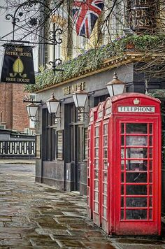 London Travel Inspiration - Red telephone boxes outside a pub in Greenwich, London on a rainy day.