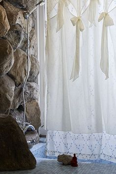 Is this a pool? A bath? Breezy curtains and surrounding rock wall, with a statue.