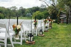 Aisle Décor at the Winvian in Morris CT Mason jars with astilbe, magnolia, pheasant feathers, dahlia's, ranunculus, viburnum berry hung by black satin ribbon on shepherd hooks. Alternated every other aisle with logs and lanterns, by Azalea Floral Design