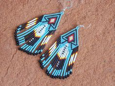 Southwestern Native American Beaded Feather Fridge Earrings In The Cherokee Colors with Sterling Silver Ear Wires by LJ Greywolf These beaded feather fridge dangle earrings are made up of tiny glass b