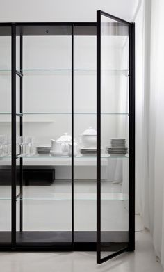 The fully glass encased Ex-libris bookcase designed by Piero Lissoni is available in unit sizes from 4 feet to 15.8 feet long