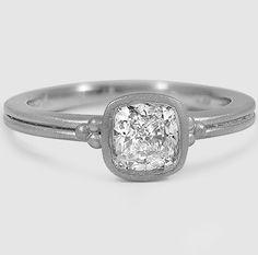 A gorgeous cushion cut diamond in a bezel setting.
