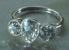 Ladies platinum ring set with three diamonds. The center diamond is a pear shape with two round diamonds set on the sides. Made of platinum wire, all the diamonds are bezelset.