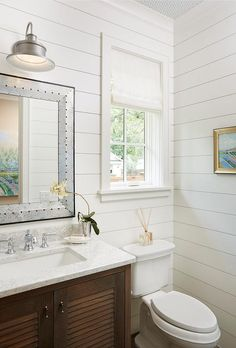 Chic cottage bathroom features shiplap walls lined with a brown louvered washstand topped with white and gray marble under a beveled rivet mirror illuminated by a galvanized metal sconce.