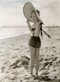 De Amerikaanse filmster Mary Carlisle kijkt gekleed in badpak en met grote strandhoed op lachen achteruit op het strand. Verenigde Staten, 1933.