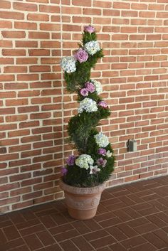 Our spiral juniper is gorgeous when accented by a bride's floral palette. This bride used purple roses, blue hydrangea and orchids in their palette. We took those flowers and wrapped the spiral juniper with them to accent the William & Mary Alumni House.