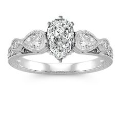 This sophisticated vintage inspired engagement ring features two stunning pear-shaped diamonds, at approximately .28 carat TW, and 18 round diamonds, at approximately .17 carat TW. Set in quality 14 karat white gold with beautiful hand-engraved and milgrain detailing, the total carat weight is approximately .45 carat. Add the center diamond of your choice to complete this eye-catching piece.