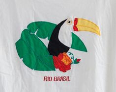 Super cute vintage retro white toucan Rio Brasil t shirt. It has very vibrant colors that are embroidered on to the fabric. This is a great shirt to pair with your favorite jeans! Very soft, comfortable, with a wide scoop neck. Label: No label Tag Size: None Fits like a womens xs/small. // M E A S U R E M E N T S : L A Y I N G F L A T // Shoulder to Shoulder: 16 Shoulder to Hem: 21 Bust: 34 Waist: 35