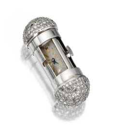 PLATINUM AND DIAMOND PURSE WATCH, PAUL FLATO, CIRCA 1935 The cylindrical case concealing a revolving rectangular dial with baton numerals and blued steel hands, the bombé terminals pavé-set with single-cut diamonds, dial signed Flato, movement by M. Tissot.