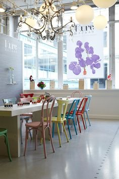 white table, mis-matched colourful chairs