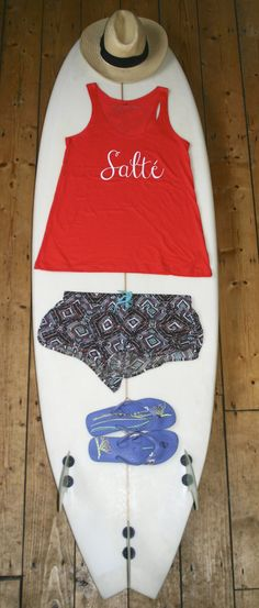 Flat Lay on surfboard - surf style - featuring Salt Clothing Company Salte coral vest and tribal print shorts. Love this look for the summer!