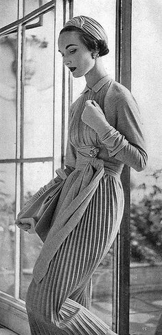 Evelyn is wearing a beige pleated tube with a wide boned sash of wool jersey crepe by Claire McCardell, photo by Henry Clarke Vogue July 1953