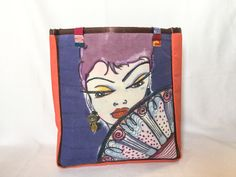 """Zelda - Because A Woman Needs To Be Mysterious Sometimes This bag measures 15"""" wide by 17"""" high by 6"""" deep The image is painted and dyed on linen Zelda is a wearing golden dangling earring The back and sides are a rich orange fabric The inside is a fun dots on a field of pink lining fabric A 5"""" x 7"""" open side pocket All seams are tailored with pretty brown ribbon 9"""" multi-colored woven straps"""