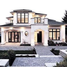 Stunning home exterior. White stucco Mediterranean / French style with upstairs balcony.