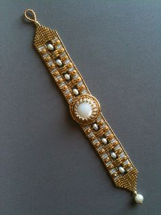 White & Gold Mother of Pearl and Freshwater Pearl bracelet by Jeka Lambert. Seed bead woven, bead embroidery. Mother of pearl cabochon, freshwater pearls, 24K gold plated beads, metal heishi disks, seed beads.