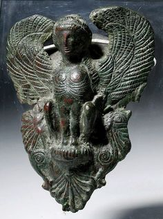 Greece, 5th century BCE.  Classical Greek bronze Siren, once an attachment to a world-class bronze vessel.  Shown facing frontal, wings spread framing her face, legs tucked under body seated upon her haunches atop a palmette.  The Siren, a mythological creature combining woman and bird, is depicted here with a bird's body and a woman's head. She is shown frontal, with her pair of arched wings spread out in symmetrical ornamental composition, framing the head in between their pointed ends…