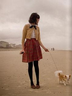 Brown loafers, red tartan plaid skirt, white blouse, black bow, mustard yellow cardigan.