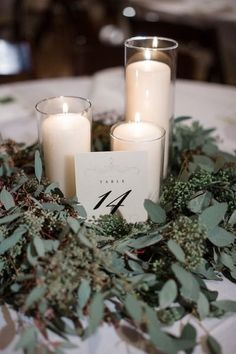 Winter wedding centerpiece idea - greenery wreath with white candles + elegant table number {JOPHOTO}