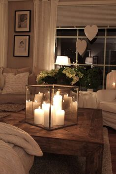 Glass cube filled with different size pillar candles... feels very warm and inviting.