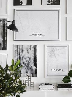 To create a thoroughly modern corner: place an interesting collection of prints and accessories on a white sideboard, then add some green plants and a minimalist candle holder.